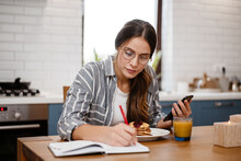Woman Writing Down Notes And U...