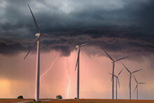 Modern Windfarm Located On Farmland In Midwest America During A Lightening Storm