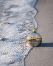 Christmas Ball Decoration In The Sand On Tropical Shore.