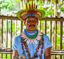 Ecuador. A Shaman From The Siona Community In His Traditional Costume Stands Model For A Photo. Taken In The Amazonian Territory Near Puerto Bolivia On The Cuyabeno River