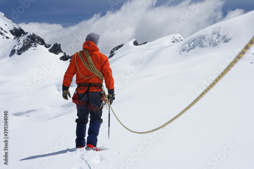 Fotografie, Obraz Hiker Connected To Safety Line In Snowy Mountains