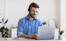 Handsome Young Man In Headset Study Online, Watching Webinar On Laptop