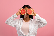 Vitamins For Beauty And Skin Care. Happy African American Woman Covering Eyes With Grapefruit Halves On Pink Background