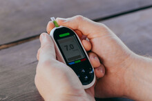 Medicine, Diabetes, Glycemia, Healthcare And People Concept - Man Checking Blood Sugar With Glucometer And Test Strip At Home.