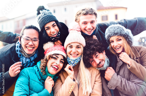 Obraz Multiracial friends taking selfie with open face mask and winter clothes - New normal friendship concept with milenial people having fun together outside - Bright filter with focus on central woman - fototapety do salonu