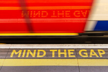 Blur Of London Underground Train And Mind The Gap Warning Sign On Tube Station Platform Edge, London, UK