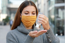 Close Up Of Young Woman With Protective Mask Using Alcohol Gel Sanitizer Hands In Modern City Street