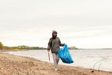 Young Female Environmental Volunteer In Cap And Hood With Trash Picker And Bag Walking On Sea Coast And Collecting Rubbish
