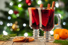 Two Glass Of Christmas Mulled Wine Or Gluhwein With Spices And Orange Slices On Rustic Table Against The Christmas Tree. Traditional Drink On Winter Holiday