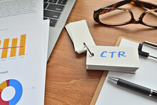 On Top Of The Notebook And Clipboard Is A Wordbook And Pen With The Word CTR Written On It. It Means Click Through Rate.