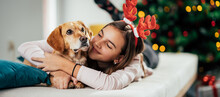 A Teenage Girl With Deer Antlers Hugging Her Dog While Lying On The Bed