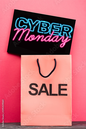 placard with cyber monday lettering near shopping bag on pink, stock image