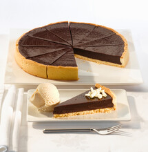 Chocolate Torte For Twelve Servings In A Pastry Case With A Scoop Of Vanilla Ice Cream