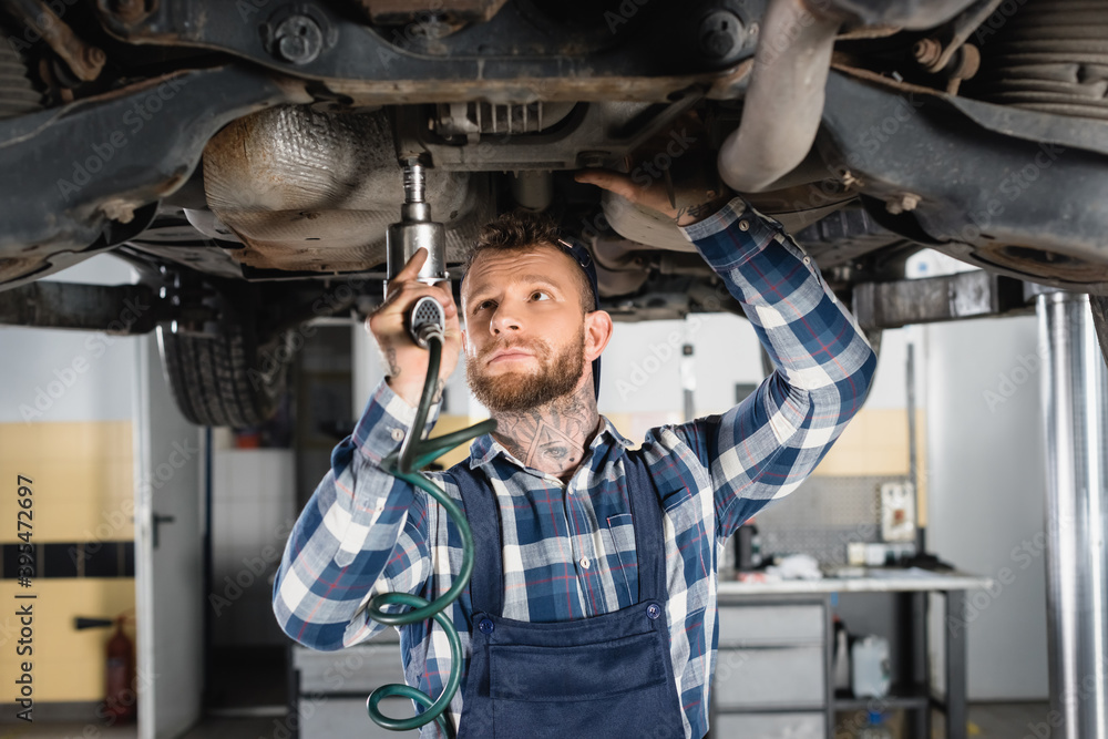 Leinwandbild Motiv - LIGHTFIELD STUDIOS : mechanic fixing detail with pneumatic wrench while standing under raised car, stock image