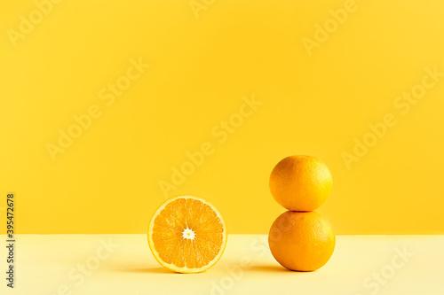 Citrus fruit orange on yellow background. Art trendy minimalist still life. Healthy lifestile. Vitamin C.