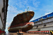 Wide Angle View Of A Weathered Cargo Ship Moored At A Dock Yard Under Maintenance And Repair In Shipyard.