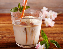Almond Milk With Vanilla Ice Cream And Coffee Ice Cubes In A Glass With A Straw And Mint