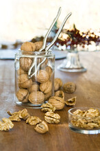 Organic Walnuts, Whole And Cracked, In A Jar With A Nut Cracker On A Wooden Table