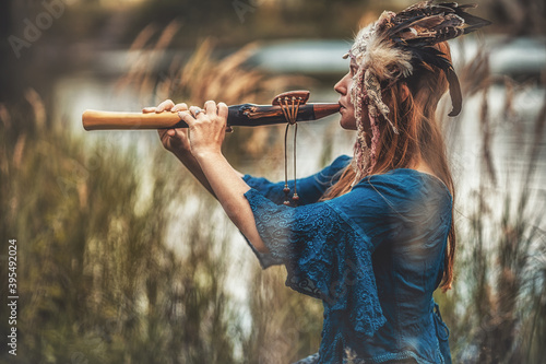 Fotografie, Tablou beautiful shamanic girl playing on shaman flute in the nature.