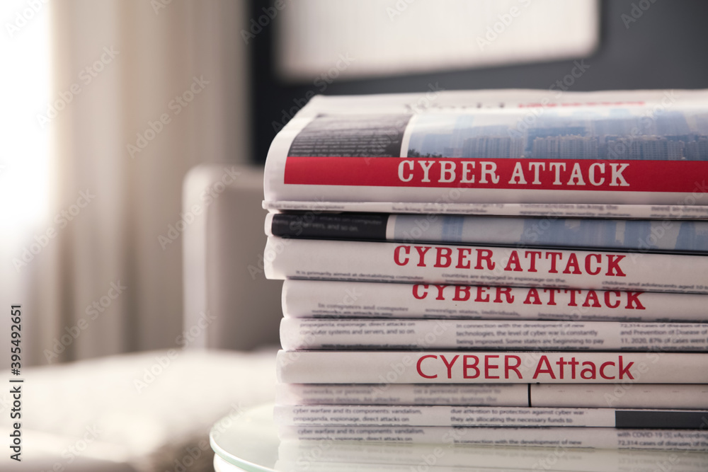 Fototapeta Stack of newspapers with headlines CYBER ATTACK on table indoors, closeup