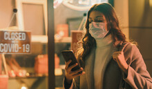 Shop Closed Due To Coronavirus Outbreak And Woman Connecting With Her Smartphone