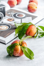 Fresh Peaches With Leaves, Book And Camera In The Background