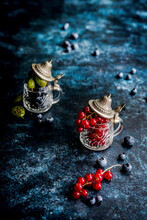 Red Currants, Blueberries And Gooseberries In Small Cups