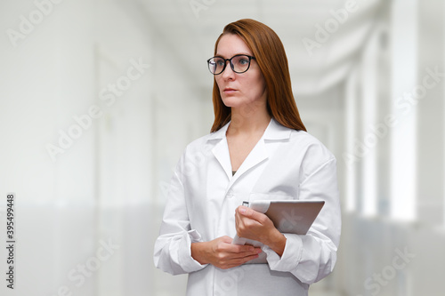 Female doctor in white robe stands in the hall of the hospital Canvas Print