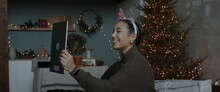 Mixed Race Female Having A Video Call With Friends Or Family On Christmas Eve. Holidays Celebration During COVID-19 Coronavirus Isolation Lockdown