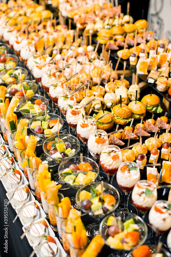 Fotografija Vertical photo of a lot of delicious desserts and aperitives on a party table