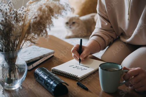 Obraz 2021 goals, new year resolution, planning. Woman writing in Notebook with text 2021 loading on the table in apartments with cat. Notepad list concept, hand writting text 2021 and loading scale - fototapety do salonu