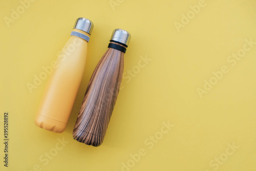 Slika na platnu Reusable eco friendly metal water bottles on yellow background