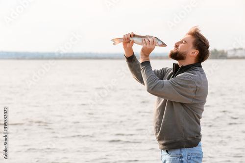 Slika na platnu Happy young man with caught fish near river