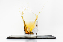 Glass Of Yellow Cold Drink With Falling Ice Cube And Splashes