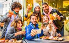 Group Of Young Millennial Friends Making A Toast While Making A Selfie Celebrating Christmas Wearing Warm Winter Clothes.students Having Fun In A  Outdoors Open Bar At Sunset.friendship And Lifestyle