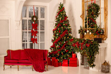 New Year's Red And Gold Interior With A Large Spruce Tree, A Red Sofa, A Fireplace And Red Boxes With Gifts