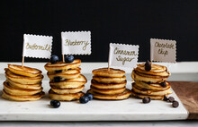 Stacks Of Mini Pancakes With Signs, Fruit And Chocolate Chips, On A Marble Board