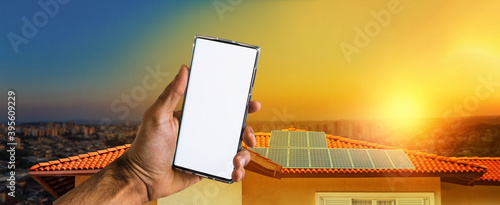Fotografie, Tablou Male hands holding a mobile with solar energy photovoltaic panel at background