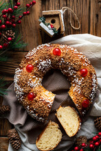 Homemade Round Bread With Hole Decorated With Sprinkles And Cherry Placed On Wooden Table With Christmas Decoration