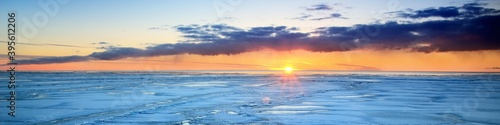 Obraz Panoramic scenery of the snowy sea shore at sunset, large ice fragments close-up. Breathtaking view. Winter seascape. Epic sky with glowing pink and golden clouds. Nature, seasons, climate change - fototapety do salonu