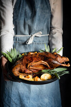 Woman Serving Roasted Duck With Fried Apples And Sage