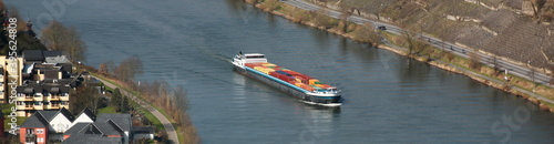 Fotografiet Inland cargo ship with colorful container freight passing vineyards and Bernkast