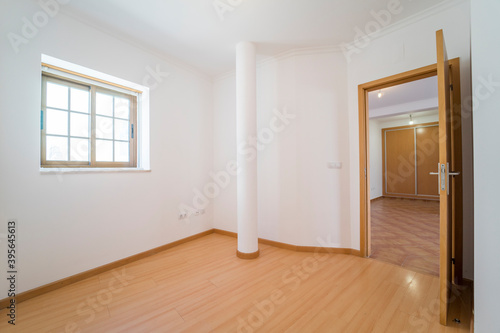 Fototapeta Empty room with wooden floating laminate flooring, door and window. House interior, wide bedroom space. Newly recently painted new apartment or house. Wood floor. Real state and property management obraz na płótnie
