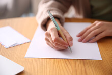 Woman Writing Letter At Wooden Table, Closeup