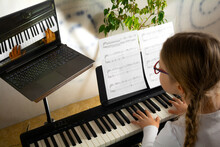 Girl Learning To Play The Piano In Distance Learning Via Laptop Over The Internet