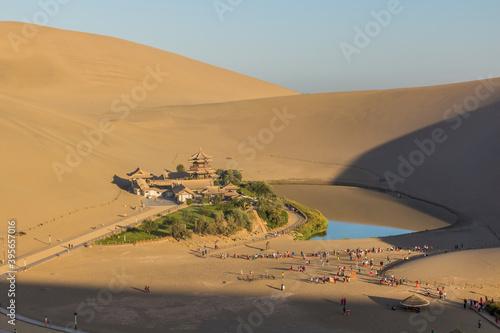 Fototapeta DUNHUANG, CHINA - AUGUST 21, 2018: Crescent Moon Lake at Singing Sands Dune near