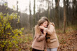 canvas print picture - Caucasian children sisters walk together in the park in the forest, girlfriends children hold hands and hug for a walk, girly secrets, autumn walks in warm coats