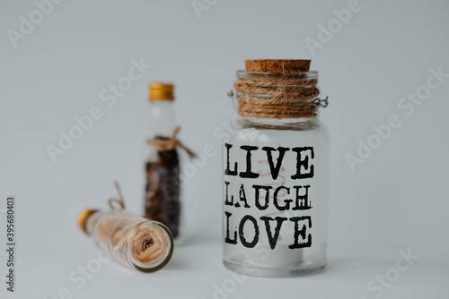 Fotografie, Obraz Closeup shot of a jar with the text live laugh love in a decoration set