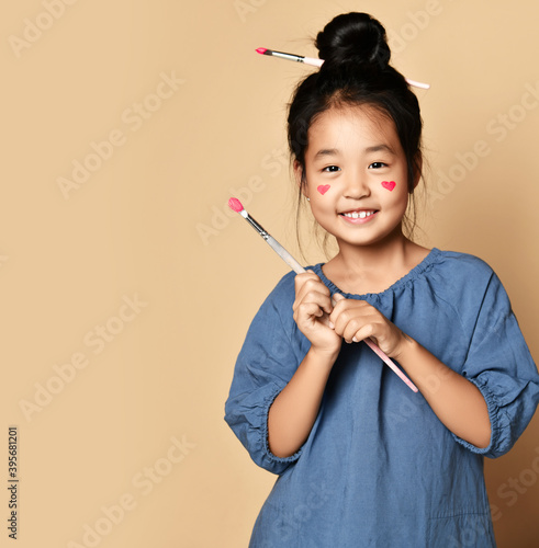 Fotografie, Tablou Cute smiling asian kid girl artist with painted red hearts on cheeks and with brush in hair and in hands over yellow wall background with copy space