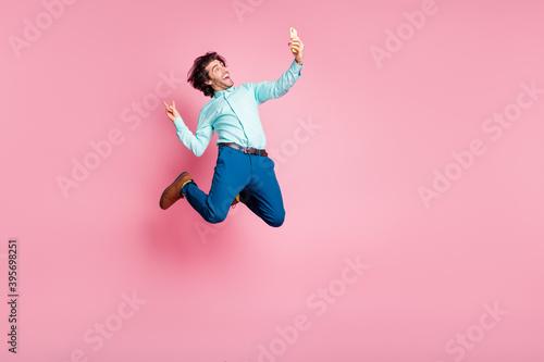 Photo Photo of astonished arab guy jumping make selfies telephone v-signing isolated p
